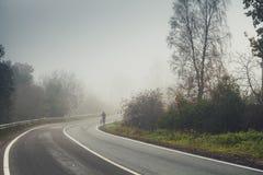 Κενή αγροτική οδική στροφή το ομιχλώδες πρωί φθινοπώρου Στοκ Εικόνες