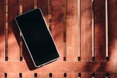 Κενή επίδειξη Smartphone που τίθεται στον ξύλινο πίνακα στοκ εικόνα