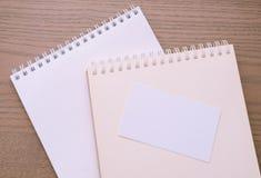 Κενή επαγγελματική κάρτα και ανοιγμένα σημειωματάρια στοκ εικόνες