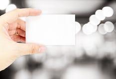 Κενή επαγγελματική κάρτα εκμετάλλευσης χεριών με ελαφριά πλάτη bokeh θαμπάδων την μπλε Στοκ Φωτογραφία