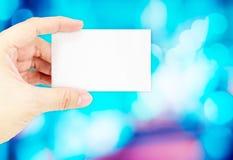 Κενή επαγγελματική κάρτα εκμετάλλευσης χεριών με ελαφριά πλάτη bokeh θαμπάδων την μπλε Στοκ φωτογραφία με δικαίωμα ελεύθερης χρήσης