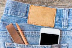 Κενή ετικέτα τζιν δέρματος τζιν παντελόνι, ξύλινο υπόβαθρο Στοκ εικόνες με δικαίωμα ελεύθερης χρήσης