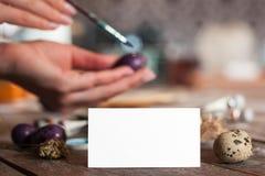 Κενή ευχετήρια κάρτα με το χρωματίζοντας αυγό χεριών Στοκ φωτογραφία με δικαίωμα ελεύθερης χρήσης