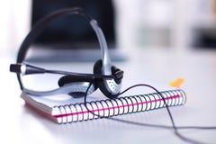 Κενή θέση εργασίας χειριστών υπηρεσιών τηλεφωνικών κέντρων Κάσκα, γυαλιά, πληκτρολόγιο και όργανο ελέγχου στον εργασιακό χώρο υπα Στοκ Φωτογραφίες