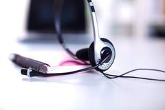 Κενή θέση εργασίας χειριστών υπηρεσιών τηλεφωνικών κέντρων Κάσκα, γυαλιά, πληκτρολόγιο και όργανο ελέγχου στον εργασιακό χώρο υπα Στοκ Εικόνα