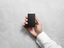 Κενή κάθετη μαύρη επαγγελματική κάρτα εκμετάλλευσης χεριών, πρότυπο σχεδίου Στοκ φωτογραφία με δικαίωμα ελεύθερης χρήσης