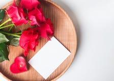 Κενή κάρτα, κόκκινα τριαντάφυλλα και διαμορφωμένο καρδιά κερί στο ξύλινο plat Στοκ φωτογραφία με δικαίωμα ελεύθερης χρήσης