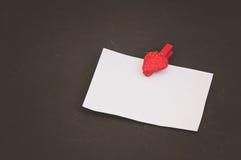Κενή κάρτα με το διάστημα για τα αρχεία στο clothespin υπό μορφή φραουλών στο μαύρο υπόβαθρο πετρών στοκ εικόνα