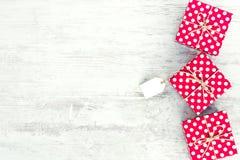 Κενή κάρτα που δένεται πέρα από το κόκκινο διαστιγμένο κιβώτιο δώρων Κόκκινα διαστιγμένα κιβώτια δώρων πέρα από το άσπρο ξύλινο υ Στοκ εικόνες με δικαίωμα ελεύθερης χρήσης