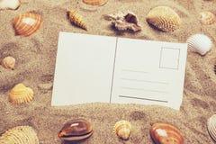Κενή κάρτα στην καυτή άμμο παραλιών με μερικά κοχύλια θάλασσας Στοκ Φωτογραφία