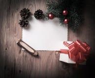 Κενή κάρτα Χριστουγέννων και ένα κιβώτιο με το δώρο στο υπόβαθρο Χριστουγέννων Στοκ φωτογραφία με δικαίωμα ελεύθερης χρήσης