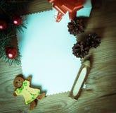 Κενή κάρτα Χριστουγέννων και ένα κιβώτιο με το δώρο στο υπόβαθρο Χριστουγέννων Στοκ εικόνα με δικαίωμα ελεύθερης χρήσης