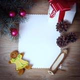 Κενή κάρτα Χριστουγέννων και ένα κιβώτιο με το δώρο στο υπόβαθρο Χριστουγέννων Στοκ Εικόνες