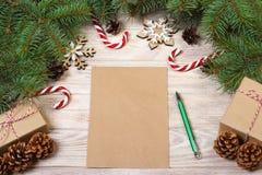 Κενή κάρτα Χριστουγέννων στον ξύλινο πίνακα με την καραμέλα Χριστουγέννων και το κιβώτιο δώρων Στοκ Εικόνες