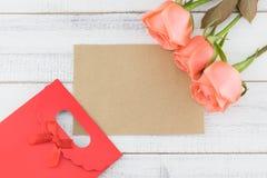 Κενή καφετιά κάρτα και κόκκινη τσάντα δώρων που διακοσμούνται με τα πορτοκαλιά τριαντάφυλλα Στοκ Εικόνες