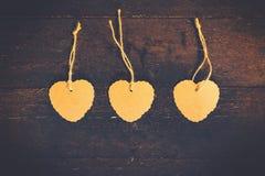 Κενή καφετιά μορφή καρδιών ετικεττών στο παλαιό ξύλινο υπόβαθρο Στοκ Εικόνες