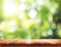 Κενή καφετιά ξύλινη επιτραπέζια κορυφή με το πράσινο BA δέντρων ήλιων και θαμπάδων bokeh Στοκ Εικόνες