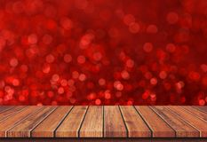 Κενή καφετιά ξύλινη επιτραπέζια κορυφή στο κόκκινο ελαφρύ υπόβαθρο θαμπάδων bokeh στοκ εικόνες