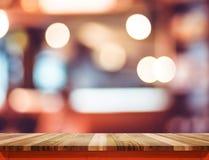 Κενή καφετιά ξύλινη επιτραπέζια κορυφή με την κόκκινη περιποίηση στο εστιατόριο θαμπάδων boke στοκ φωτογραφίες με δικαίωμα ελεύθερης χρήσης
