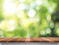 Κενή καφετιά ξύλινη επιτραπέζια κορυφή με το πράσινο BA δέντρων ήλιων και θαμπάδων bokeh Στοκ εικόνες με δικαίωμα ελεύθερης χρήσης