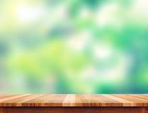Κενή καφετιά ξύλινη επιτραπέζια κορυφή σανίδων με το πράσινο υπόβαθρο δέντρων θαμπάδων Στοκ εικόνα με δικαίωμα ελεύθερης χρήσης