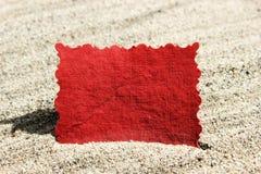 Κενή κόκκινη κάρτα σημειώσεων μηνυμάτων στην άμμο Στοκ Εικόνες