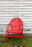 Κενή κόκκινη καρέκλα μετάλλων δίπλα στο εγκαταλειμμένο παλαιό κτήριο στοκ εικόνες