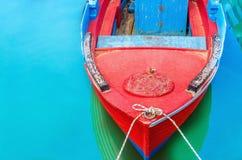 Κενή κόκκινη ξύλινη βάρκα την μπλε ομοβροντία που δένεται με στο λιμένα με το s Στοκ Εικόνα