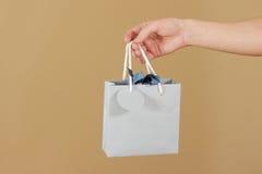 Κενή μπλε τσάντα δώρων εγγράφου με τη χλεύη καρδιών επάνω στην εκμετάλλευση υπό εξέταση Ε στοκ φωτογραφία