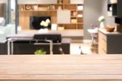 Κενή ξύλινη επιτραπέζια κορυφή με τη θολωμένη αφηρημένη χλεύη επάνω του σύγχρονου εσωτερικού καθιστικών στοκ εικόνα
