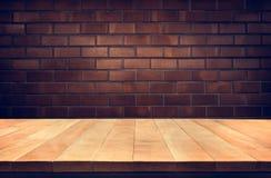 Κενή ξύλινη επιτραπέζια κορυφή με το καφετί υπόβαθρο τουβλότοιχος Στοκ εικόνα με δικαίωμα ελεύθερης χρήσης