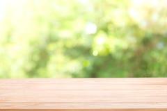 Κενή ξύλινη επιτραπέζια κορυφή με το πράσινο δέντρο ήλιων και θαμπάδων στοκ εικόνες