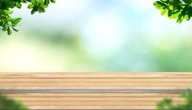 Κενή ξύλινη επιτραπέζια κορυφή σανίδων βημάτων με το δέντρο θαμπάδων στο πάρκο με το boke Στοκ εικόνα με δικαίωμα ελεύθερης χρήσης
