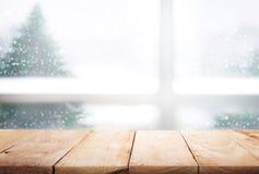 Κενή ξύλινη επιτραπέζια κορυφή στην άποψη παραθύρων θαμπάδων με το δέντρο πεύκων στο χιόνι Στοκ Φωτογραφίες