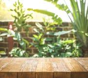 Κενή ξύλινη επιτραπέζια κορυφή στον αφηρημένους κήπο θαμπάδων και το υπόβαθρο σπιτιών στοκ εικόνες