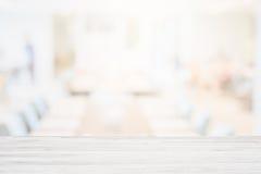 Κενή ξύλινη επιτραπέζια κορυφή στο θολωμένο υπόβαθρο καφετεριών ή το υπόβαθρο εστιατορίων καφέδων για το προϊόν montage παρόν Στοκ φωτογραφίες με δικαίωμα ελεύθερης χρήσης
