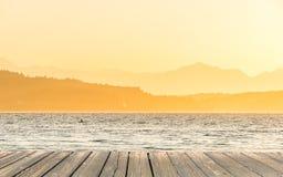 Κενή ξύλινη επιτραπέζια κορυφή γεφυρών έτοιμη για το montage επίδειξης προϊόντων με τη θάλασσα όταν υπόβαθρο ηλιοβασιλέματος Στοκ Εικόνες