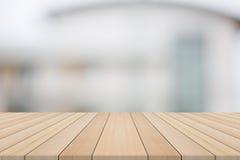 Κενή ξύλινη επιτραπέζια κορυφή στο άσπρο θολωμένο υπόβαθρο από την οικοδόμηση Στοκ φωτογραφία με δικαίωμα ελεύθερης χρήσης