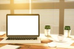Κενή οθόνη lap-top στον ξύλινο πίνακα με το φλιτζάνι του καφέ και τη χλόη Στοκ εικόνα με δικαίωμα ελεύθερης χρήσης