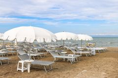 Κενή παραλία με τα άσπρα sunshades ενάντια στον ουρανό, Ιταλία, Riccione Στοκ Φωτογραφία