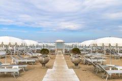 Κενή παραλία με τα άσπρα sunshades ενάντια στον ουρανό, Ιταλία, Riccione Στοκ Εικόνες