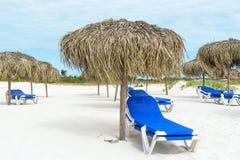 Κενή παραλία στη χαμηλή εποχή, τους αργοσχόλους ήλιων και τις ομπρέλες Στοκ Εικόνες