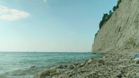 Κενή παραλία χαλικιών κάτω από τον απότομο βράχο απόθεμα βίντεο