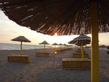 Κενή παραλία με τις ομπρέλες και sunsets Στοκ Φωτογραφίες