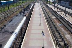 Κενή πλατφόρμα σιδηροδρόμων με το ηλεκτρικούς τραίνο και το σιδηρόδρομο Στοκ φωτογραφία με δικαίωμα ελεύθερης χρήσης