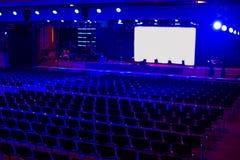 Κενή σκοτεινή σύγχρονη αίθουσα για τα γεγονότα και την παρουσίαση με την άσπρη οθόνη προβολής και το μπλε φως Preperation για την Στοκ Φωτογραφίες