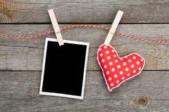 Κενή στιγμιαία φωτογραφία και κόκκινη ένωση καρδιών στη σκοινί για άπλωμα Στοκ φωτογραφία με δικαίωμα ελεύθερης χρήσης