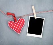 Κενή στιγμιαία φωτογραφία και κόκκινη ένωση καρδιών στη σκοινί για άπλωμα Στοκ εικόνες με δικαίωμα ελεύθερης χρήσης