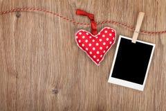 Κενή στιγμιαία φωτογραφία και κόκκινη ένωση καρδιών στη σκοινί για άπλωμα Στοκ Εικόνα
