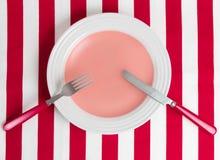 Κενή στρογγυλή ανώτερη άποψη πιάτων σχετικά με το κόκκινο γδυμένο τραπεζομάντιλο Στοκ Φωτογραφίες